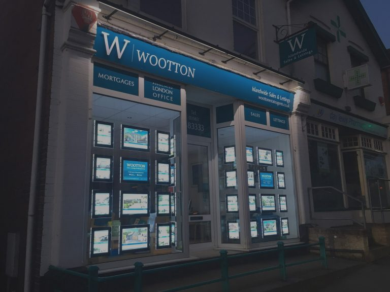 Shop front of wootton estate agents lit up at night