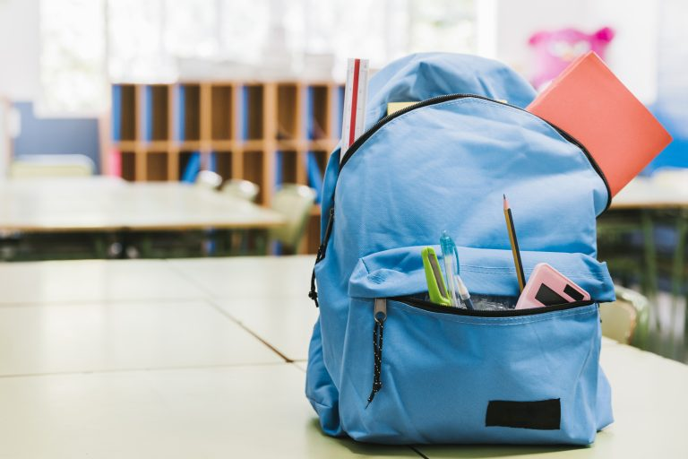 blue school backpack on table pencils and calculator hanging out of front